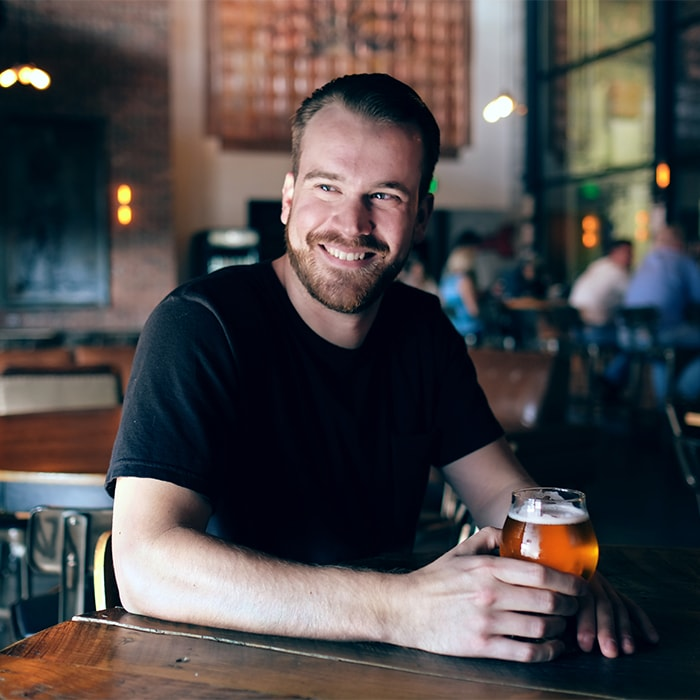 Man holds beer while smiling
