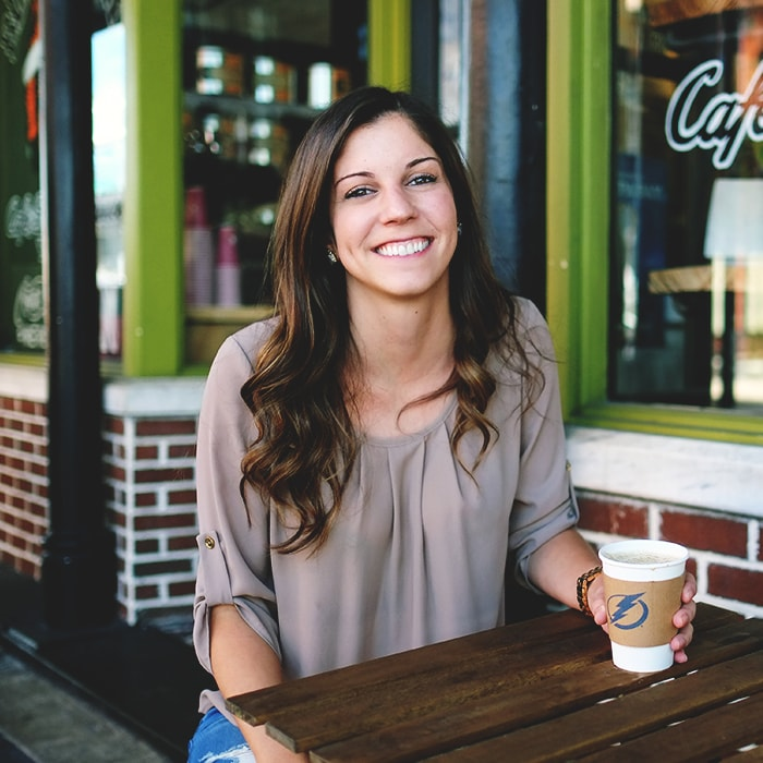 Woman holds coffee outside cafe