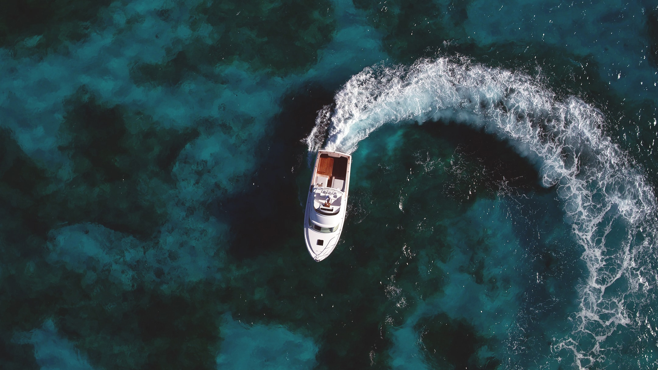 An overhead shot of a Bertram Yacht circling in water used for their brand refresh.