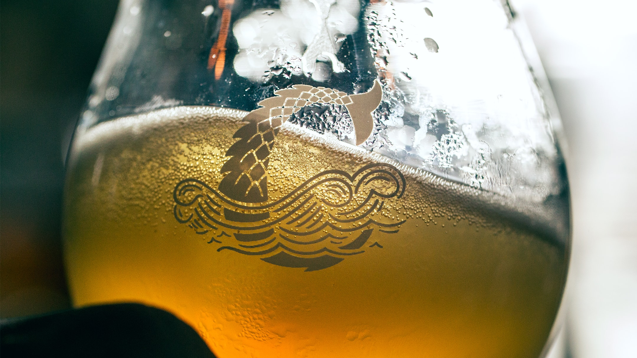 Coppertail logo on glass with beer