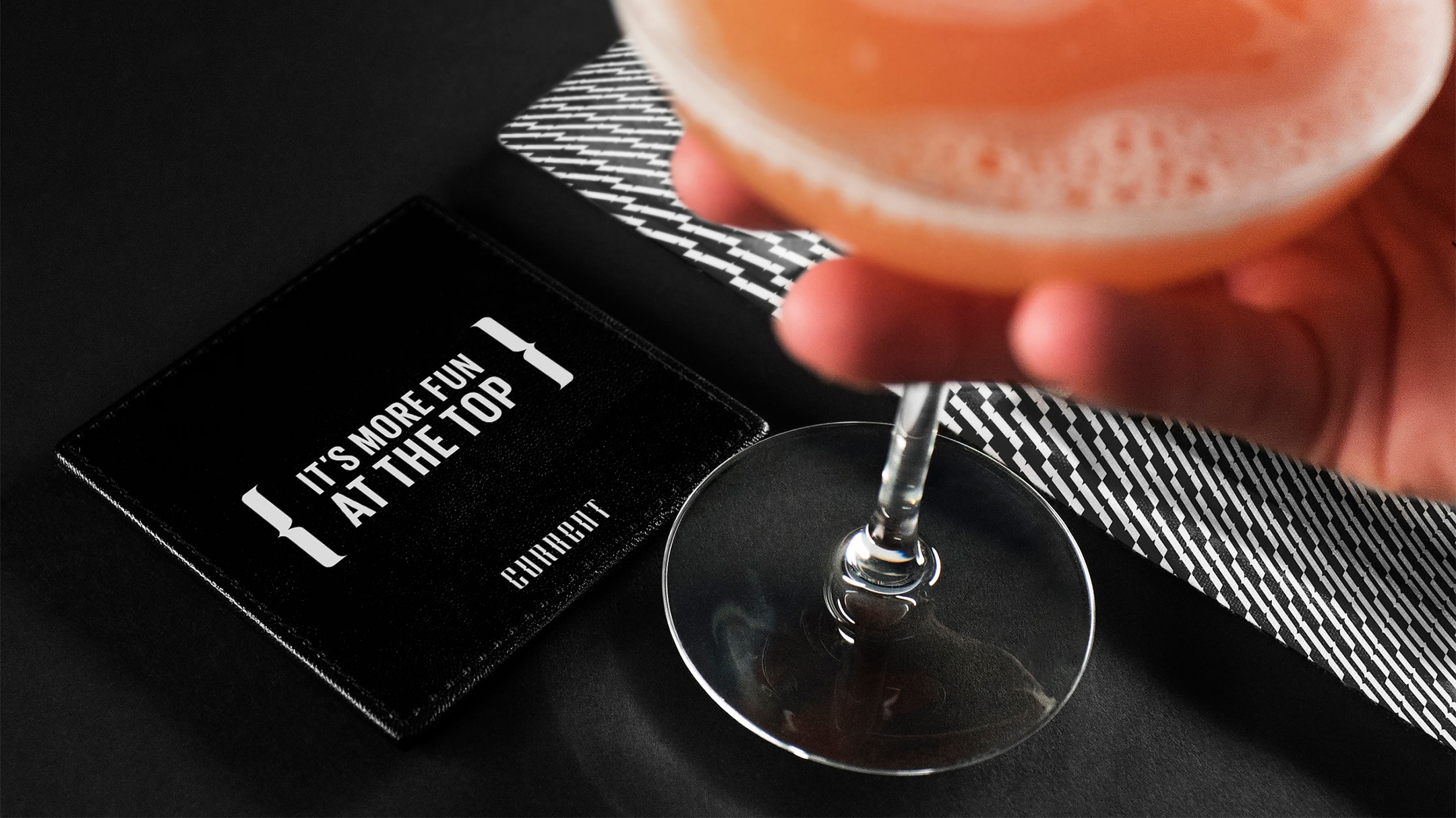 Current hotel branded coaster with a drink.