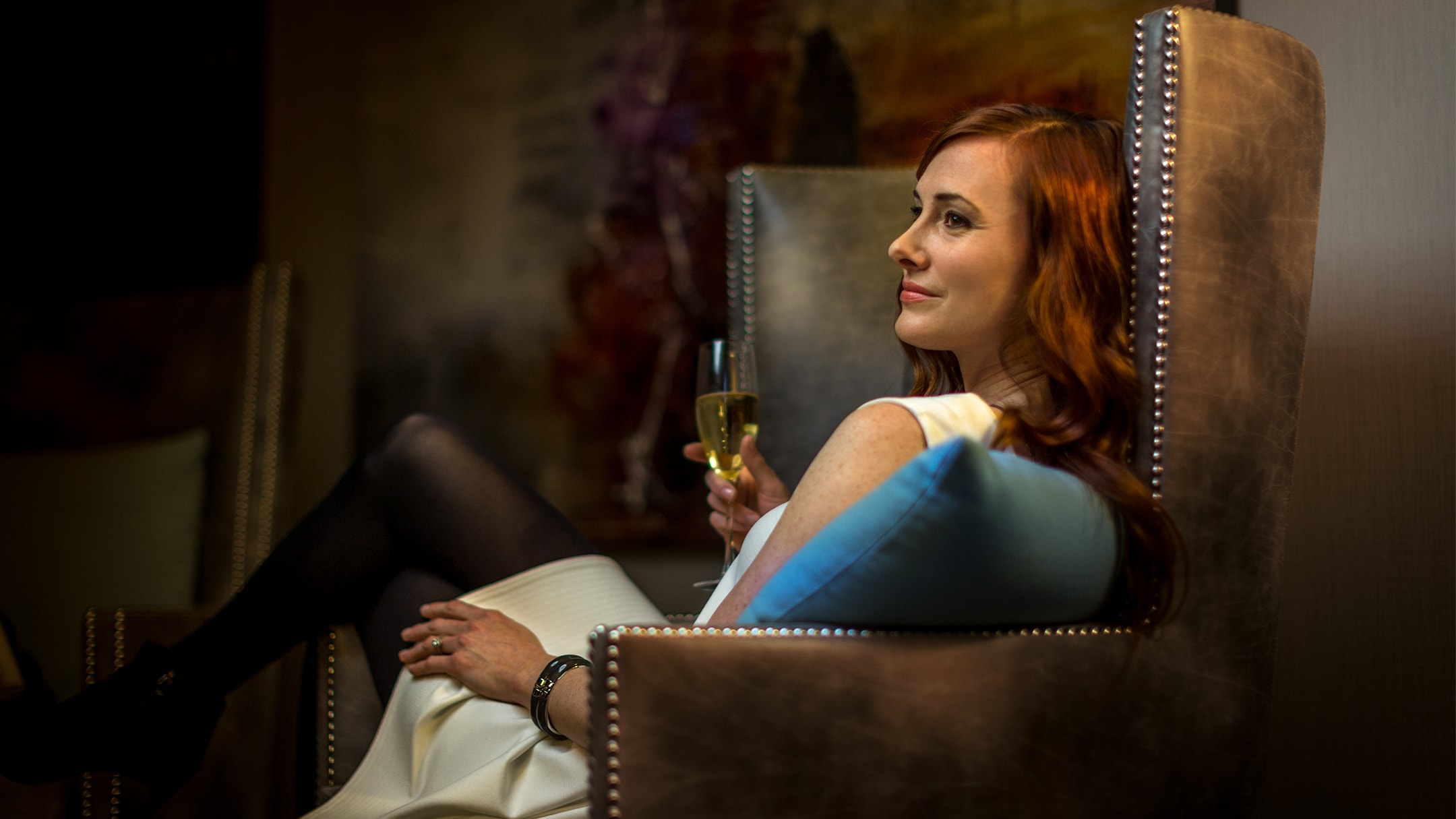 woman lounging in arm chair with champagne