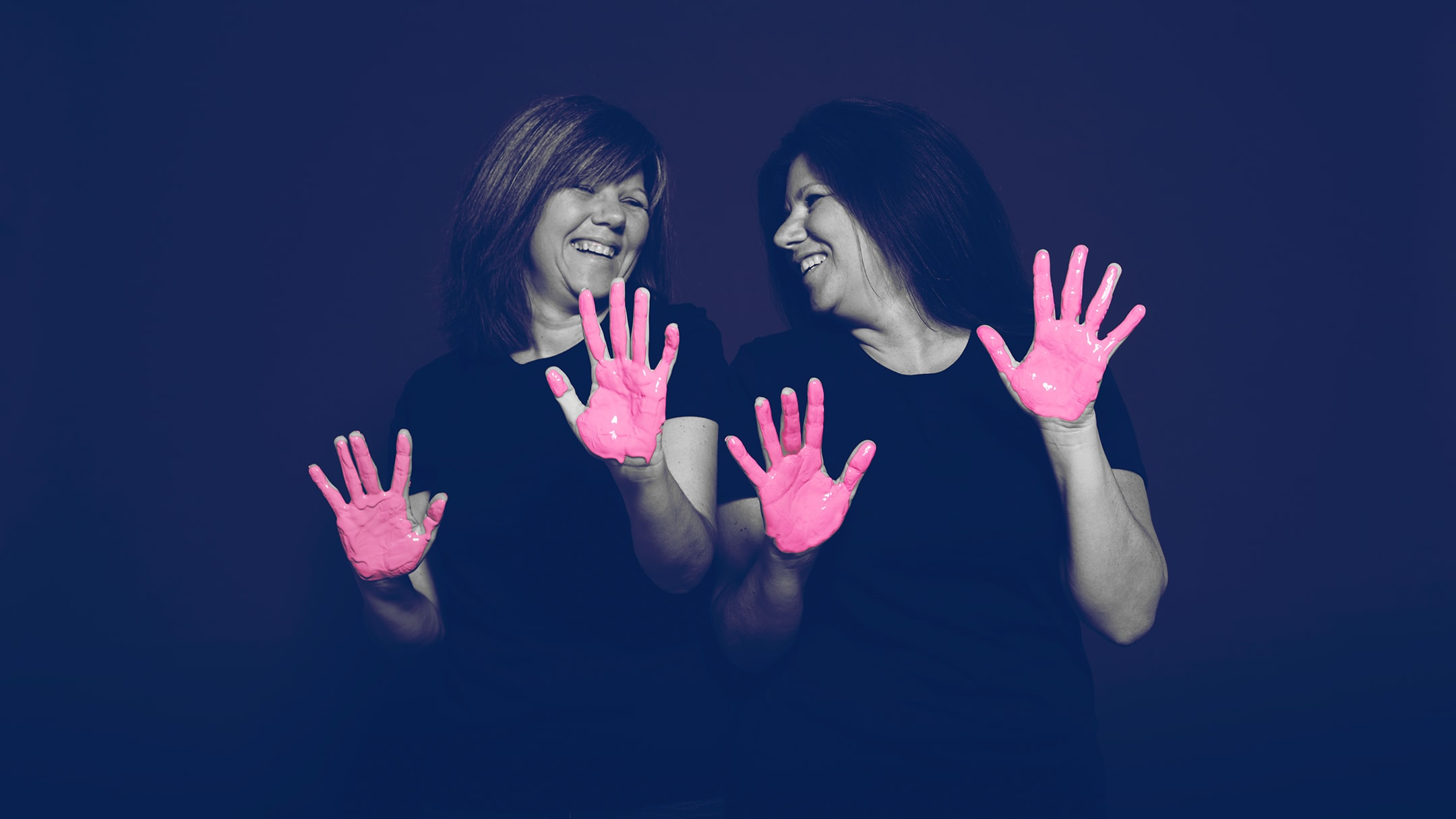 Two breast cancer survivor posing for the in our hands hospital campaign with pink paint on her hands.