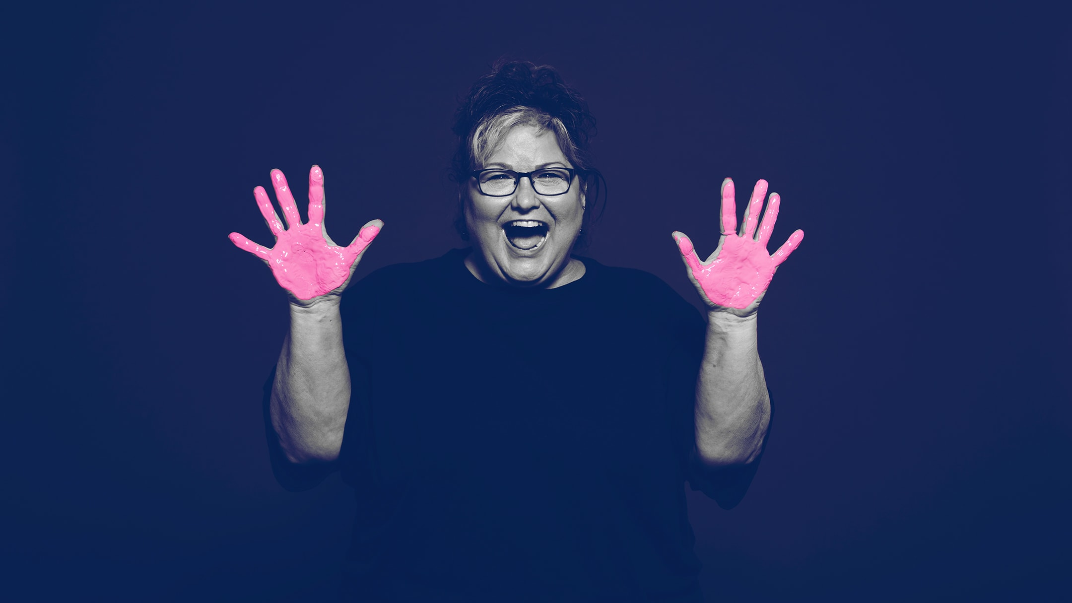 Breast cancer survivor posing for the in our hands campaign with pink paint on her hands