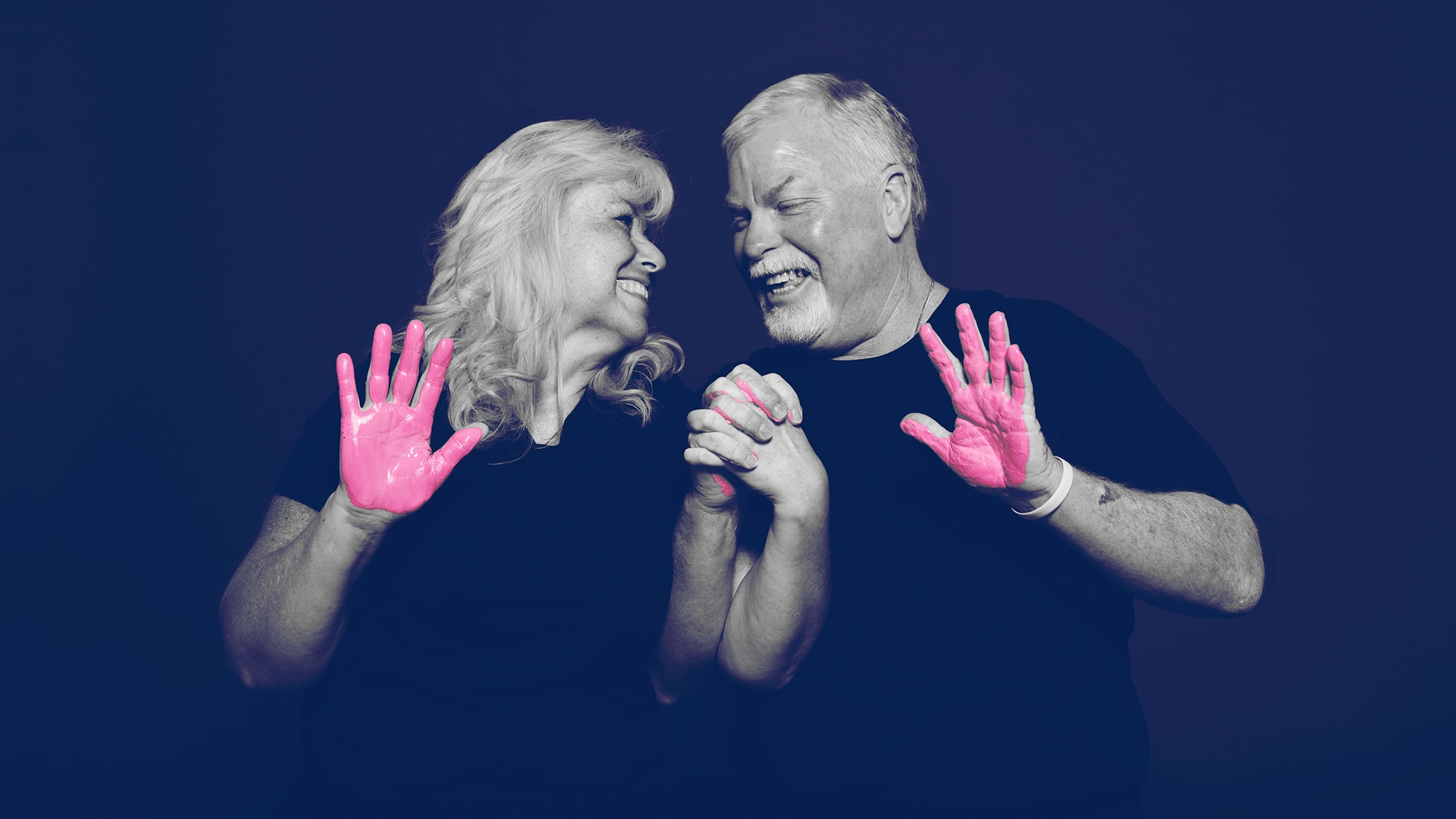 A woman and a man looking at each other and smiling with pink paint on their hands.