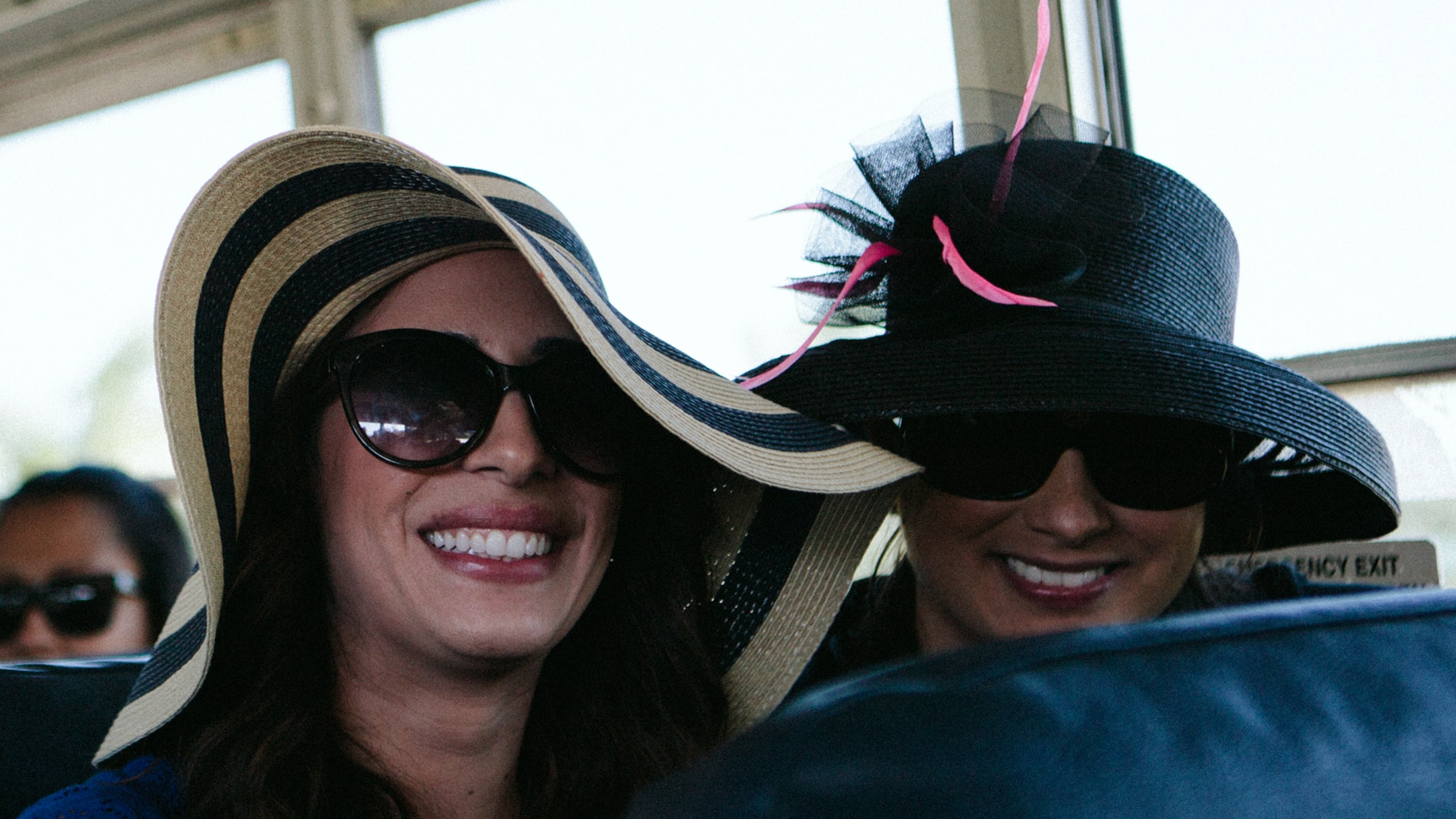 Two women on a bus smiling and wearing floppy hats.