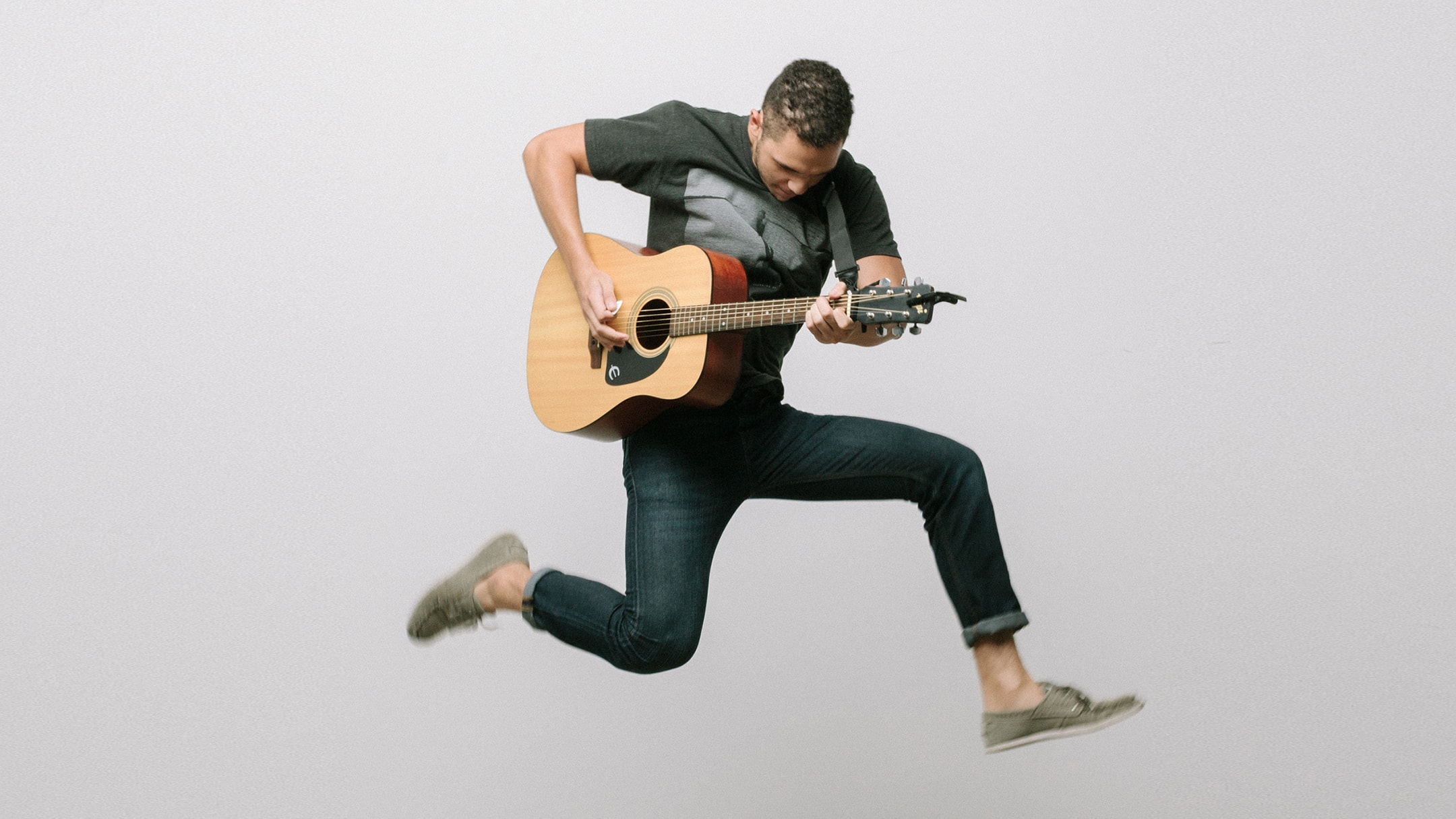 Man jumping into the air while playing guitar.