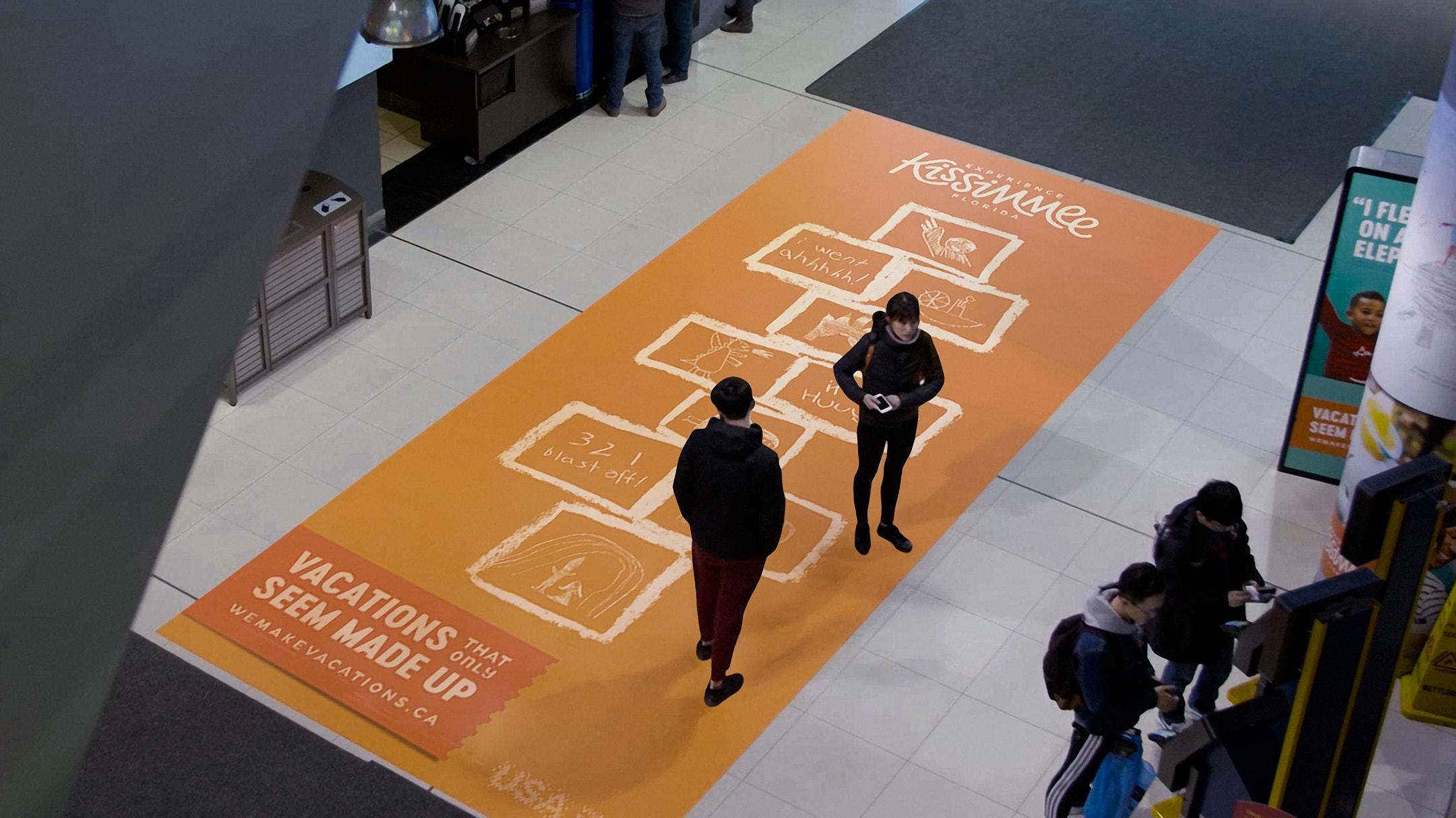 Experience Kissimmee hopscotch ad on mall floor.