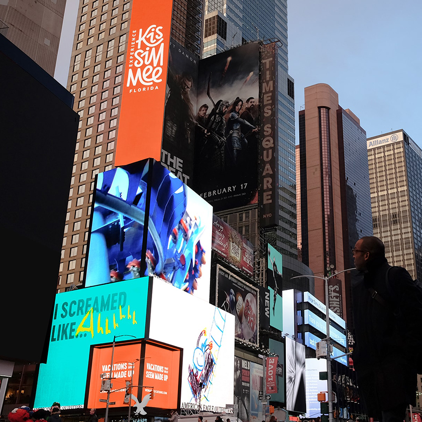 A man looking at Experience Kissimmee digital billboards in Time Square, NY.