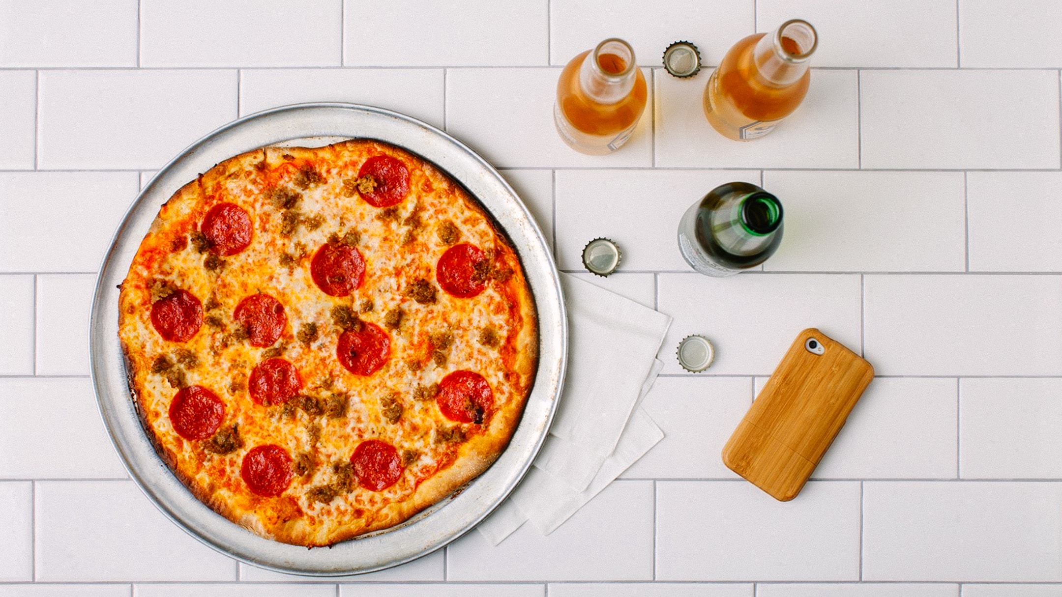 An overhead shot of of Ciccio Cali's pizza with three opened drinks on a white-tiled counter top.