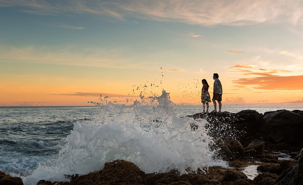 Couple standing on rocks with waves crashing