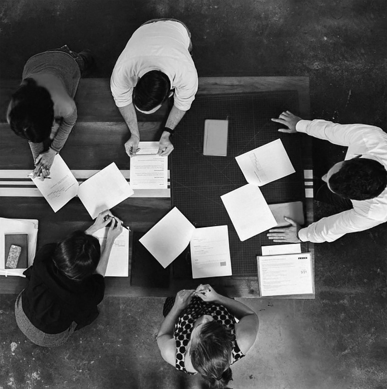 Black and white overhead shot of people working around a table.