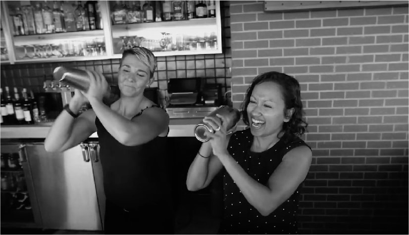 Two women shaking drink tumblers behind the bar and smiling.