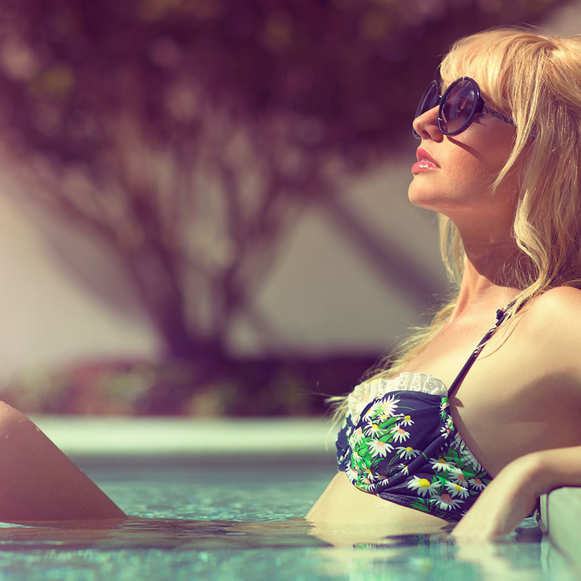 Woman relaxes in pool wearing sunglasses - a photo used to highlight our customer experience and hospitality branding services.