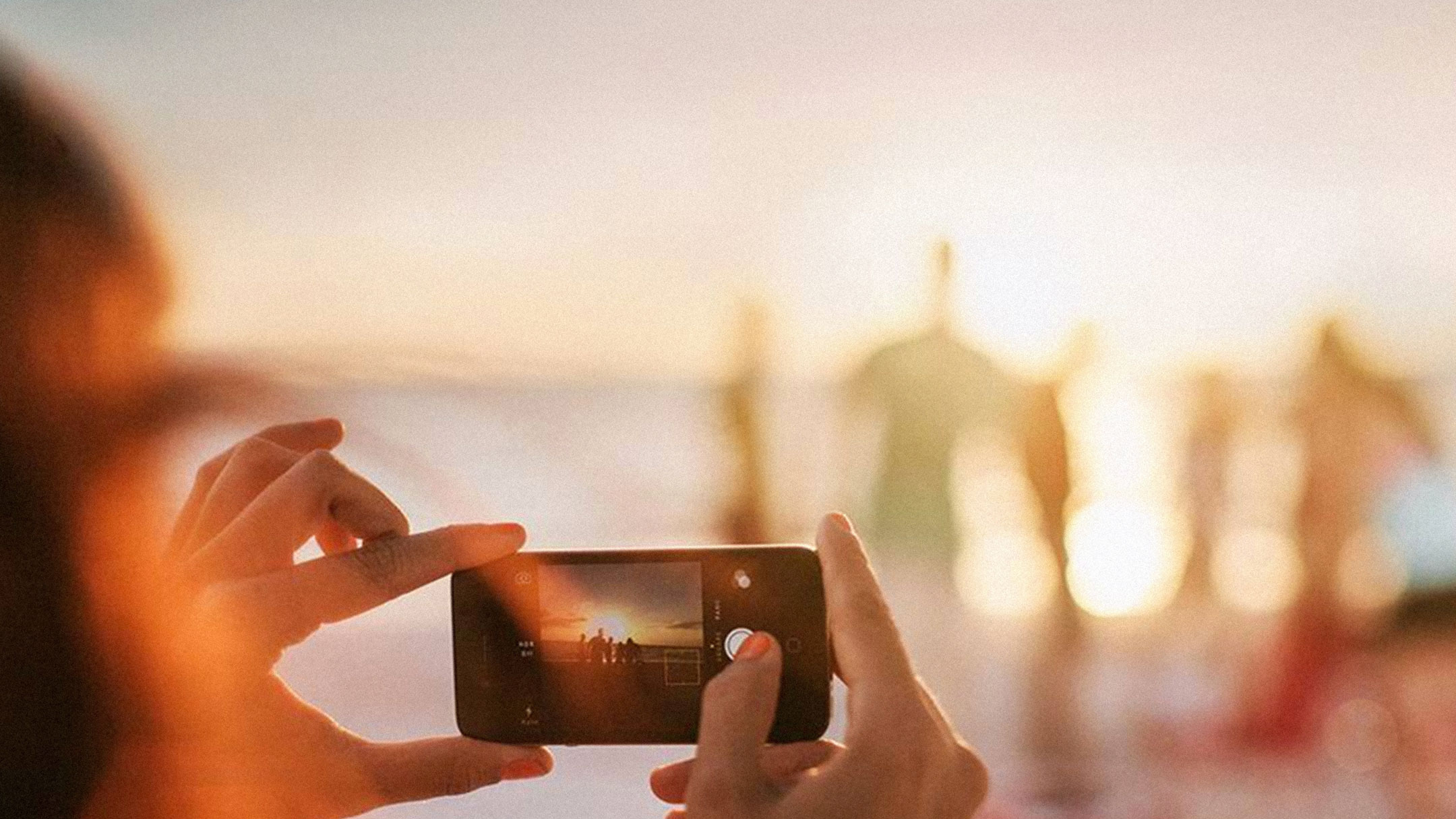 Someone taking a picture of friends on the beach with their iPhone.