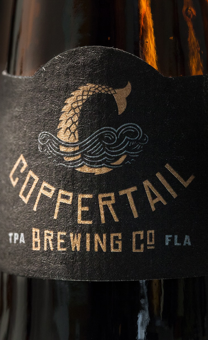 Close up of coppertail beer branding and bottle packaging design.