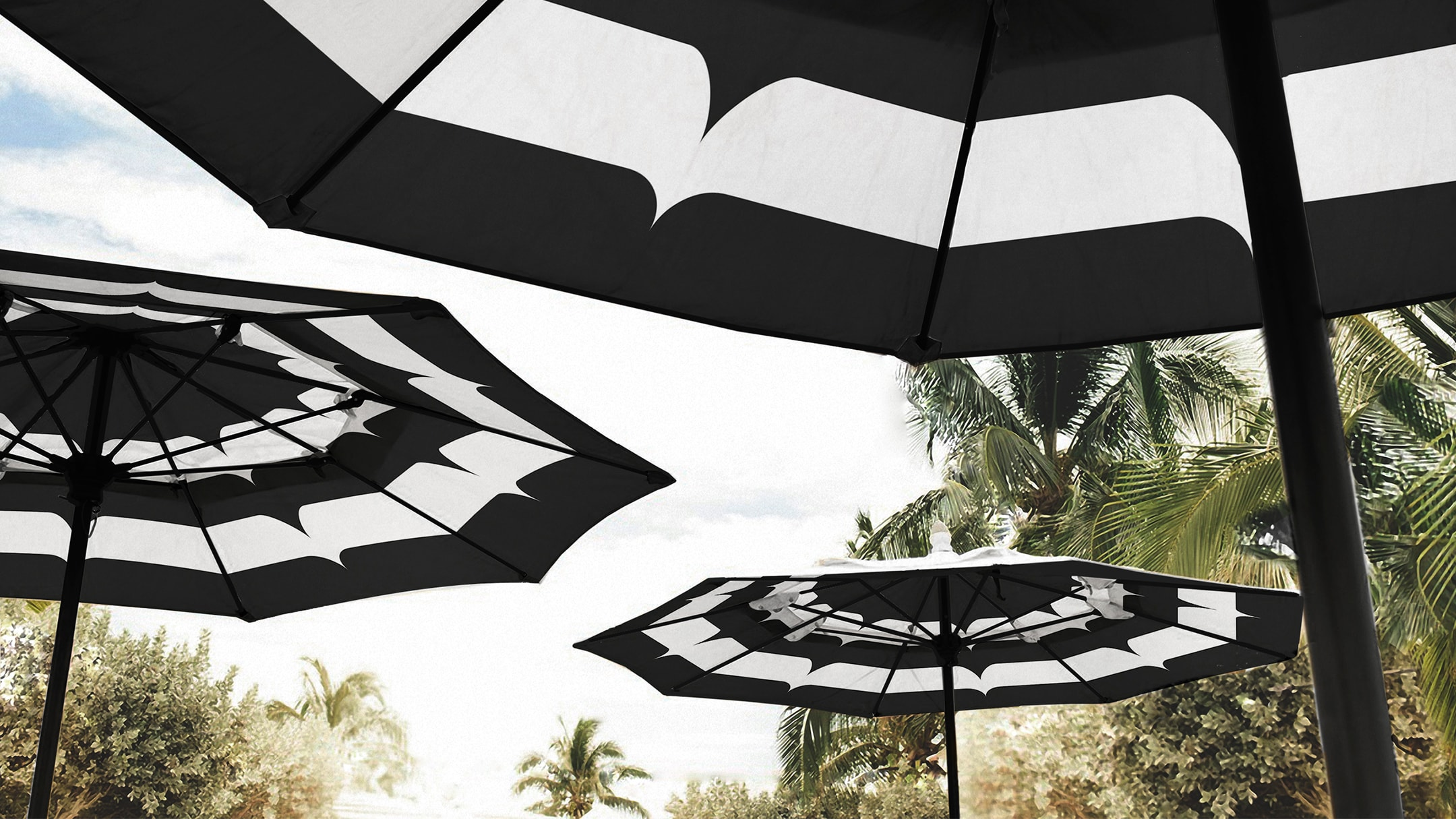 Black and white hotel pool umbrellas that feature a pattern from the Current's hotel branding.