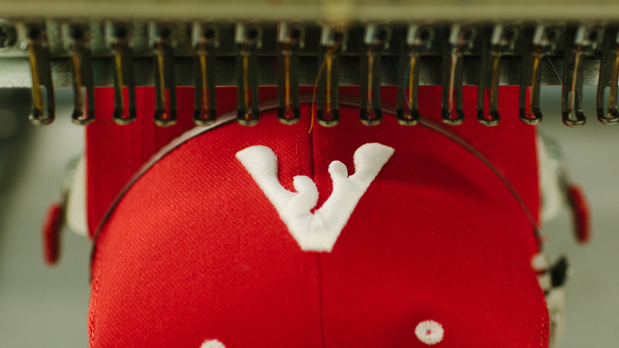Spark advertising agency - logo on a red hat being embroidered with white thread.