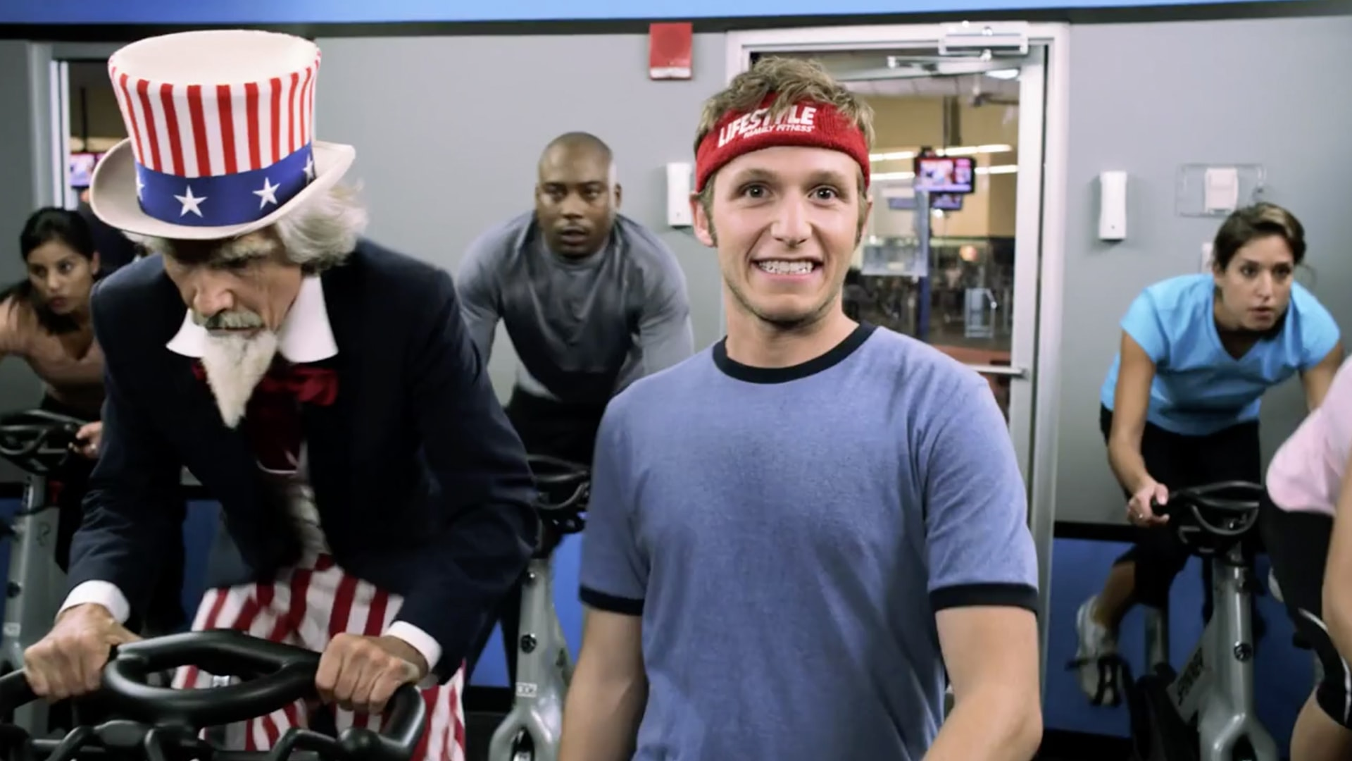 A man at the gym attending a cycling class next to someone dressed up as Uncle Sam.