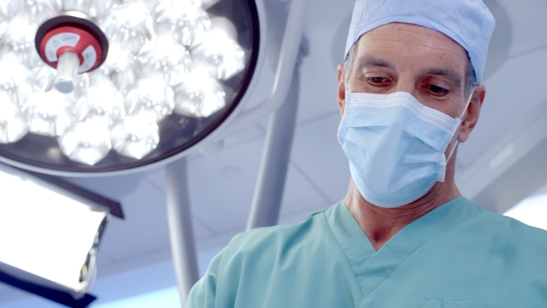 A close up of a surgeons face. He is wearing the cap, mouth guard, and scrubs. The medical light is next to him.