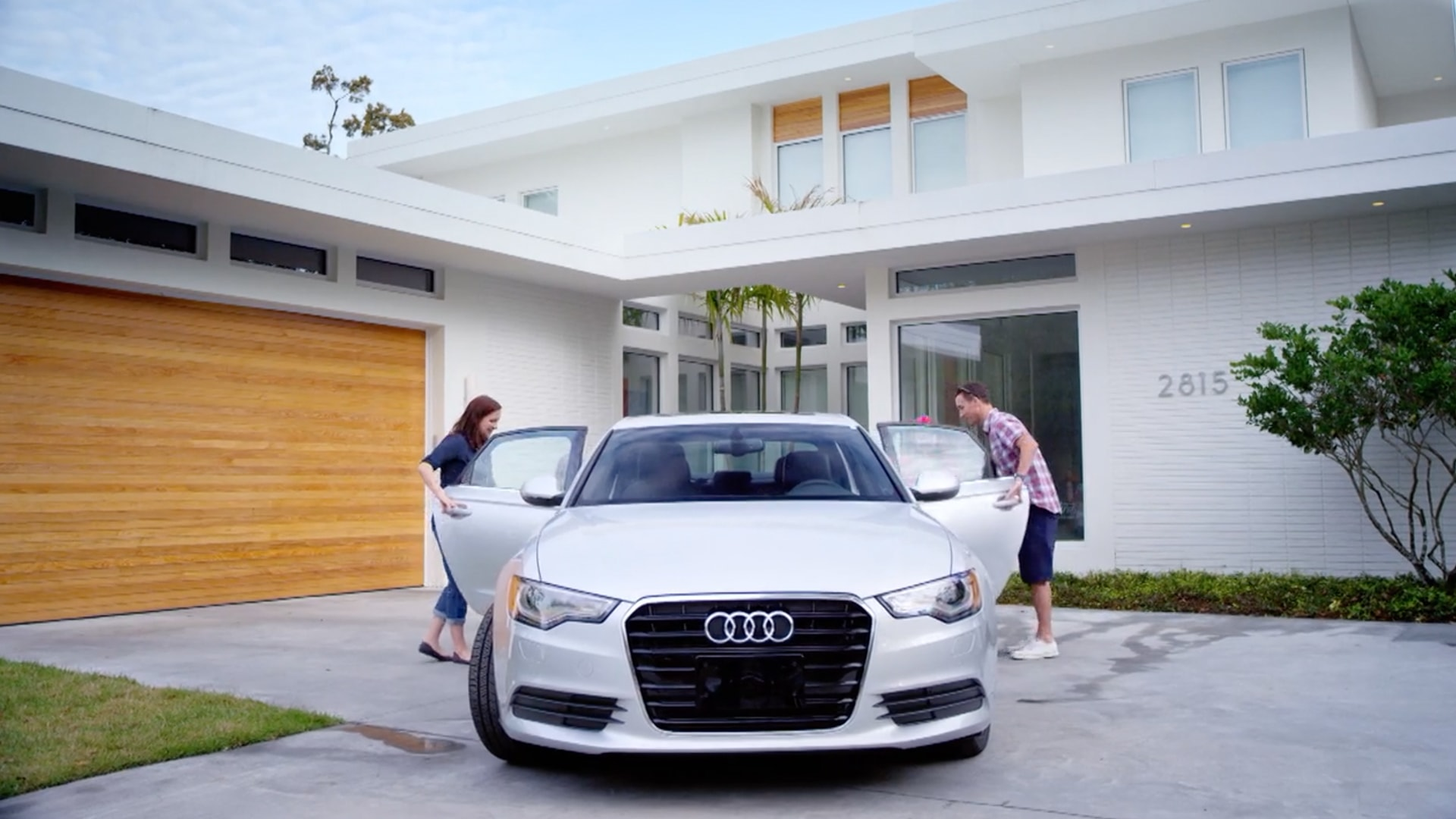 A man and woman about to get into their silver audi in front of their house.