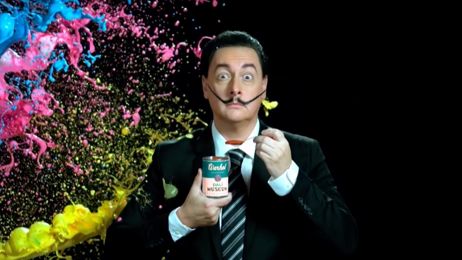 A man dressed as Salivdor Dali holding an andy Warhol soup can is about to be covered in incoming blue, pink, and yellow paint.