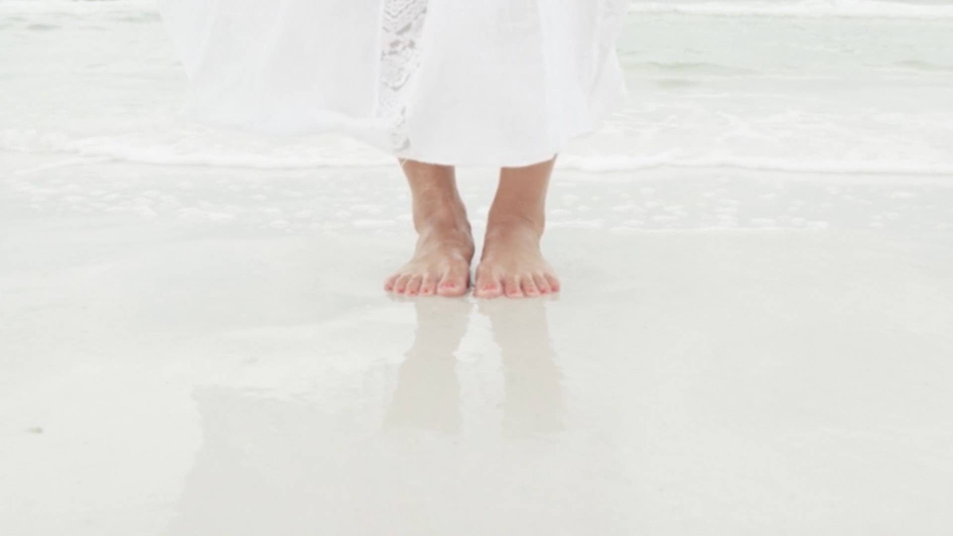 A close up of a woman's feet in the sand near the tide of the beach