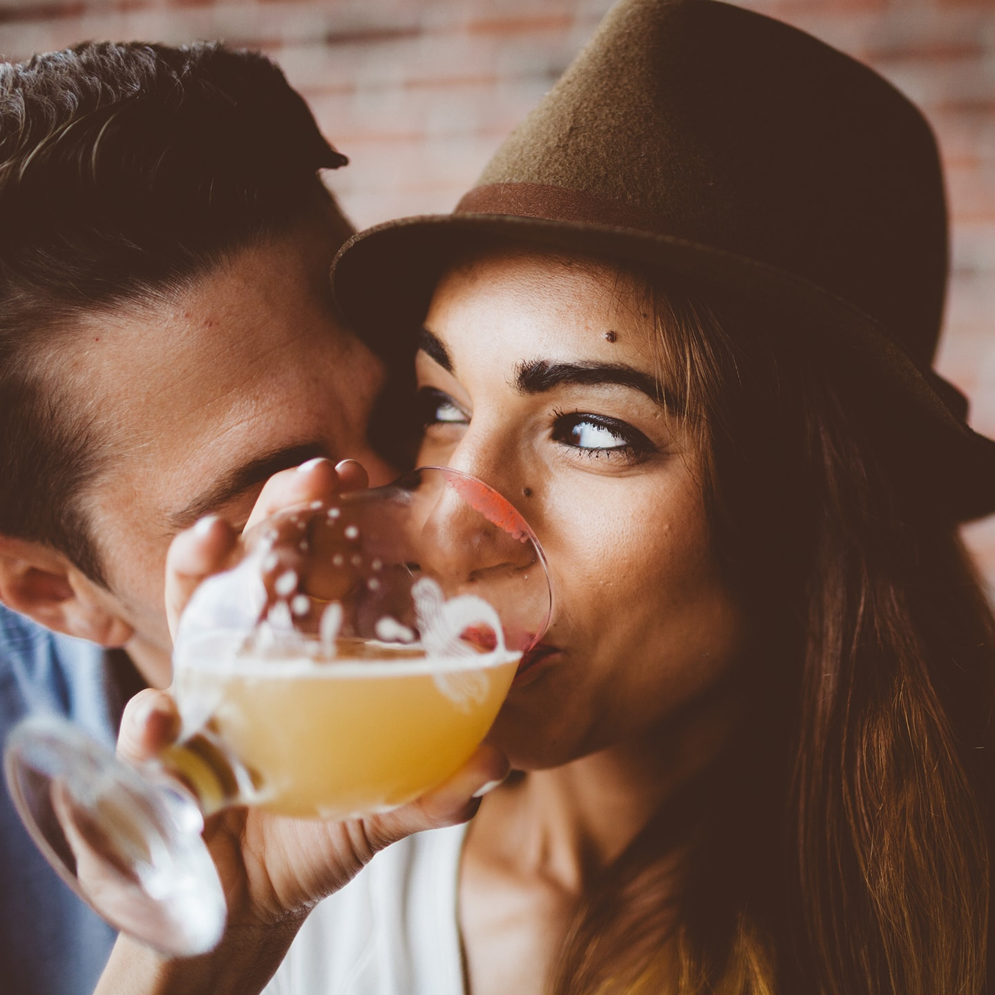A woman drinking a beer with a man kissing her on the cheek,