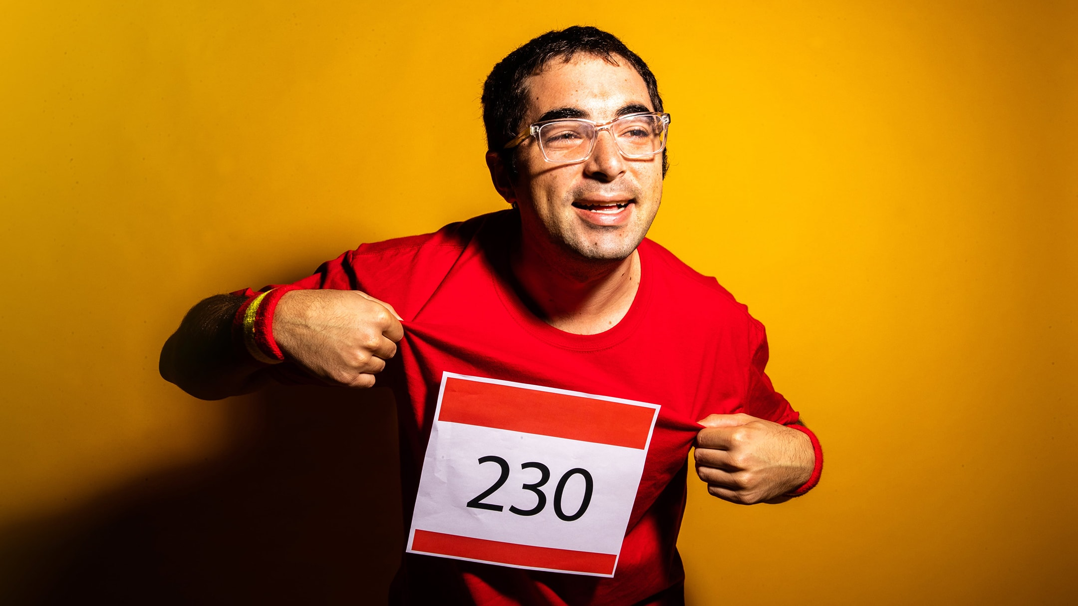 Man wearing red shirt with a marthon number on. He's smiling. This is the header image of a stick article about media.