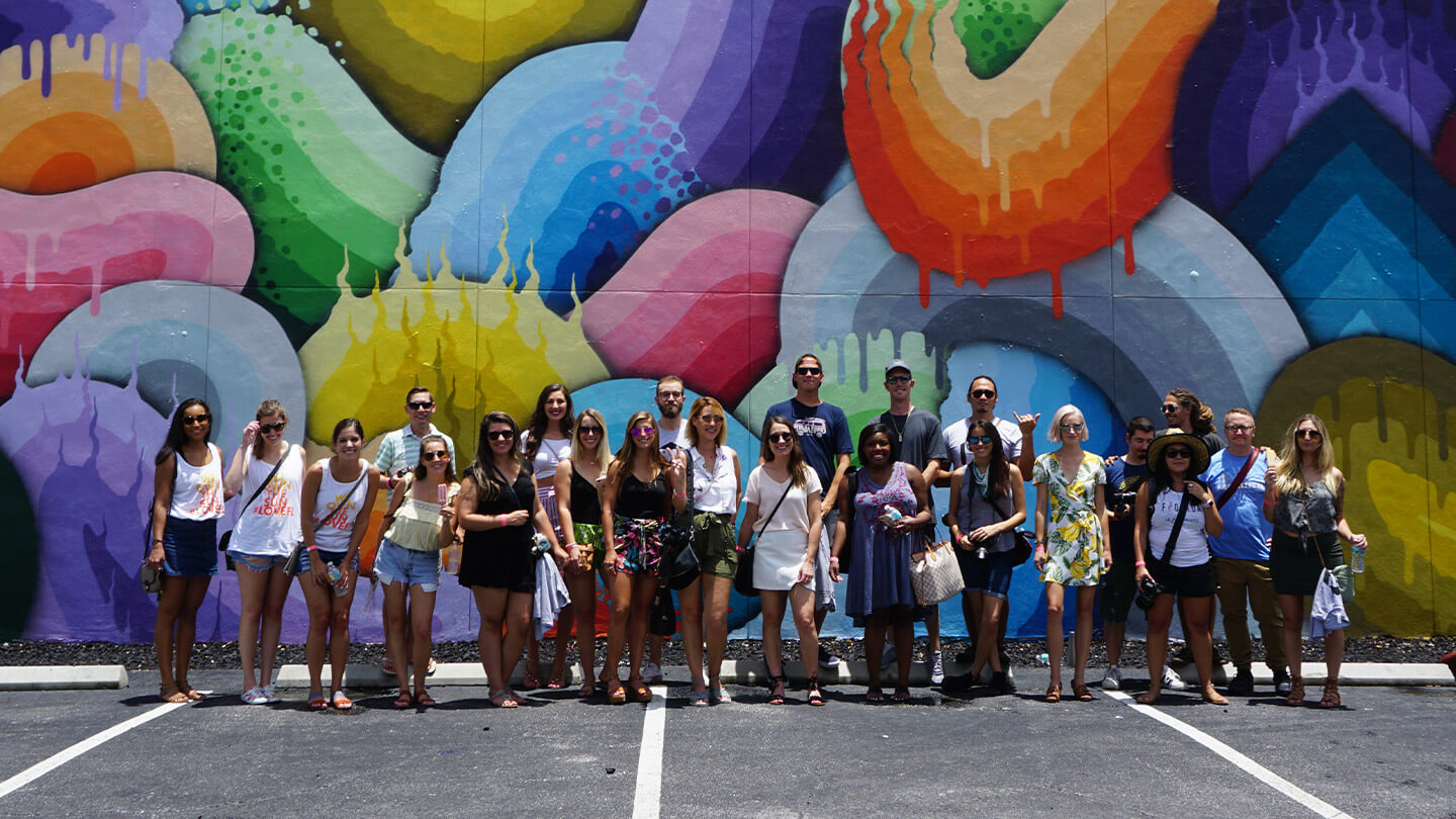 A group shot in front of a mural from our experience marketing component a Florida block party
