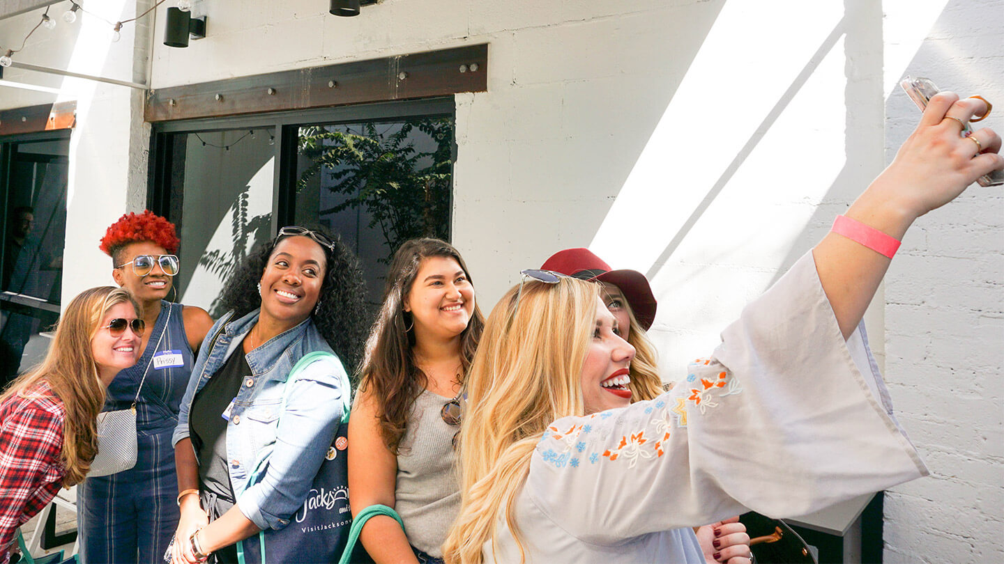 Group of people smiling and taking a selfie from our experience marketing component a Florida block party