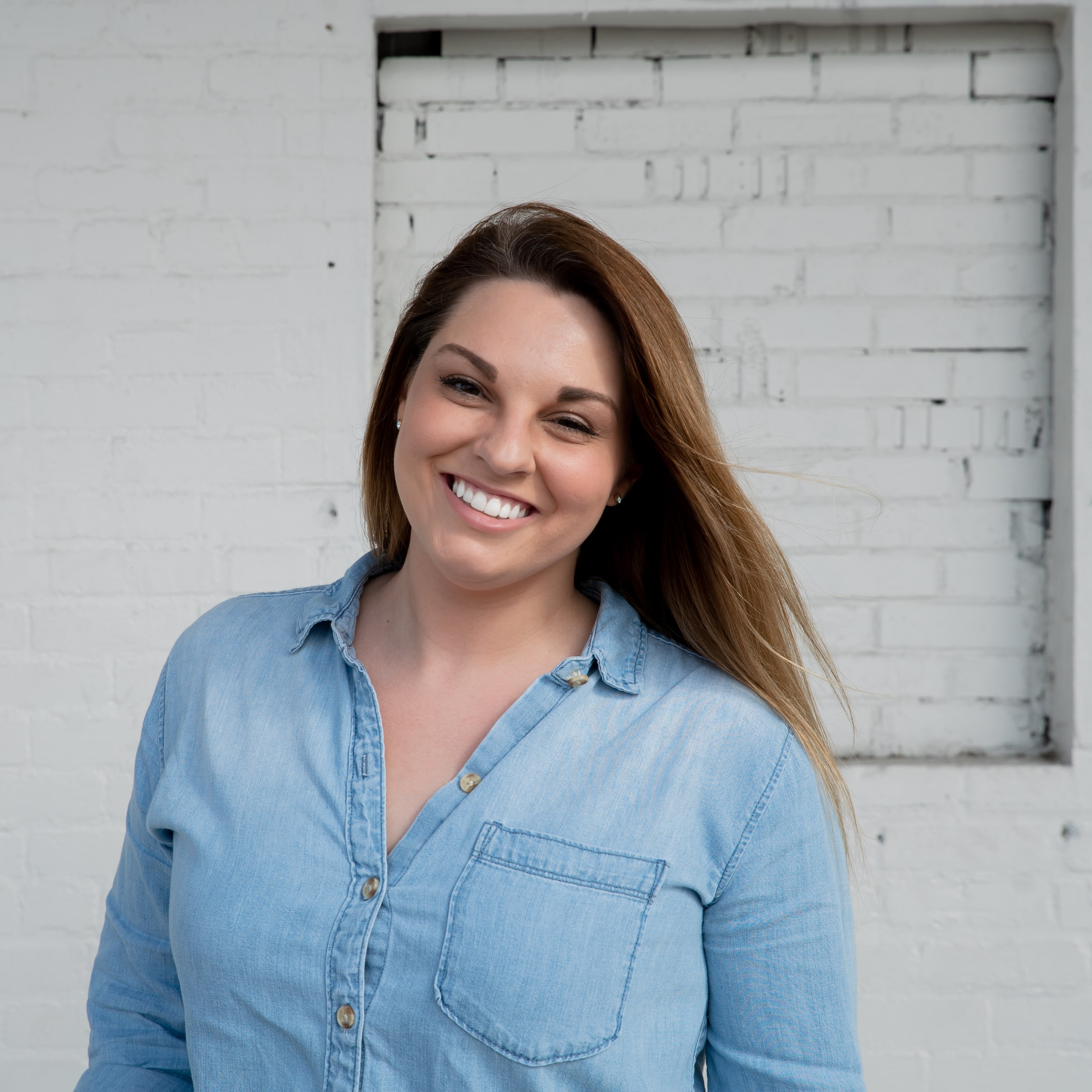 Lauren Williams, SPARK employee wearing a denim top against a white brick wall